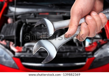 Hand with wrench. Auto mechanic in car repair . - stock photo