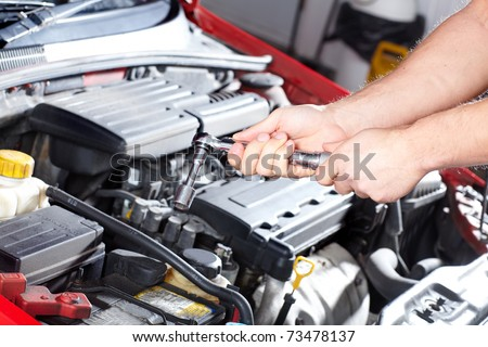 Hand with wrench. Mechanic. Auto repair shop. - stock photo