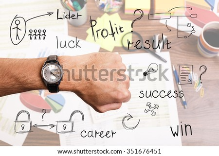 Hand with wrist watch showing precise time on the workplace background - stock photo