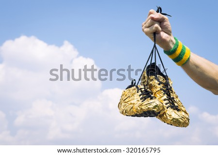 Hand with wristband holding gold running shoes against blue sky