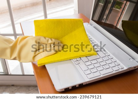 hand with yellow glove cleaning a laptop - stock photo