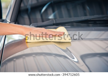 Hand with yellow microfiber cloth, cleaning car.