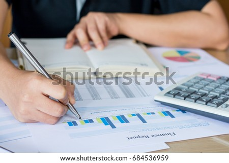 Hand woman holding pen pointing on  finance report chart and calculate finance.