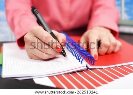 hand woman makes a note in notebook - stock photo