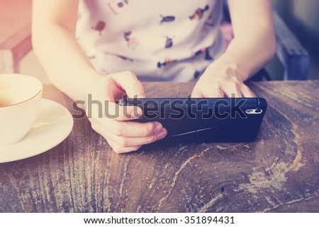 hand woman using smartphone in coffee shop and soft light with vintage filter. - stock photo
