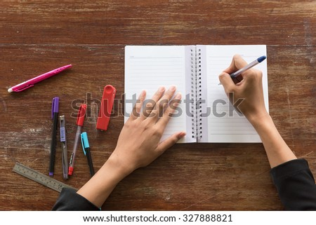 hand women writing a pen on a blank white notebook,ruler ,red stapler ,cutter with old wooden background - stock photo