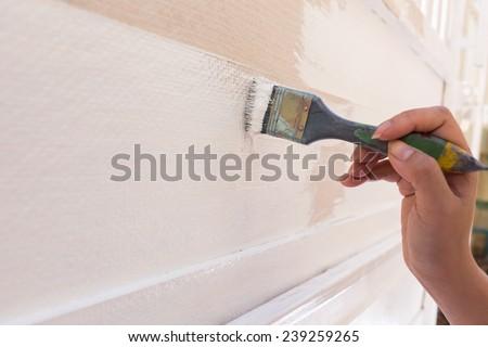 hand worker holding brush painting white on wood fence - stock photo