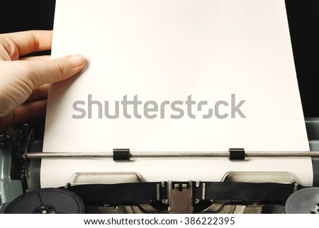 Hand working on an old typewriter with paper, close up - stock photo