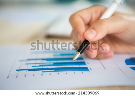Hand write on Various financial charts on the table - stock photo