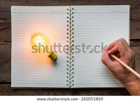 Hand write over Note book and light bulb - stock photo