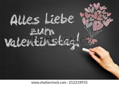 """Hand writes in German """"Alles Liebe zum Valentinstag!"""" (Happy Valentine's Day!) on blackboard - stock photo"""