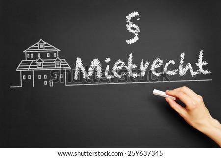 """Hand writes in German """"Mietrecht"""" (tenancy law) on blackboard - stock photo"""