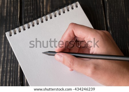 Hand writes pencil in a notebook on the aged dark wooden background