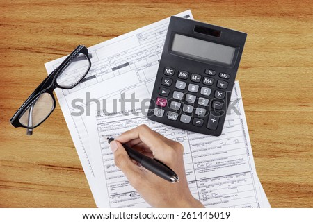 Hand writes the personal information on the health insurance claim form - stock photo
