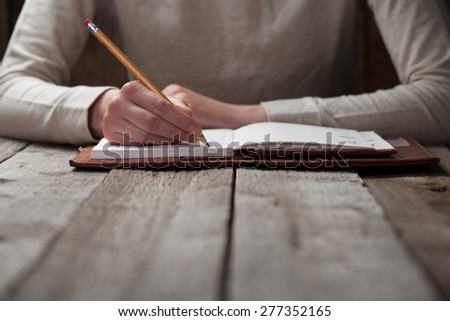 hand writes with a pen in a notebook - stock photo