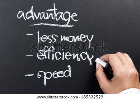 Hand writing a competitive advantage of business concept with chalk