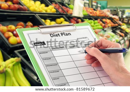 Hand Writing a Diet Plan by Supermarket Fruit - stock photo