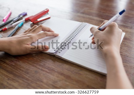hand writing a pen on a blank white notebook,ruler ,red stapler ,cutter with old wooden background