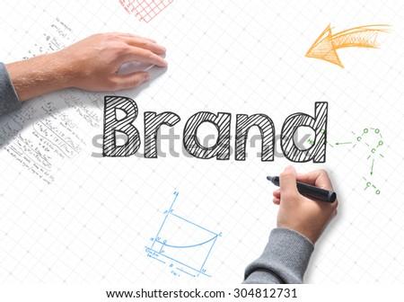 Hand writing brand on white sheet of paper - stock photo