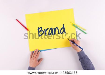 Hand writing Brand on yellow paper - stock photo