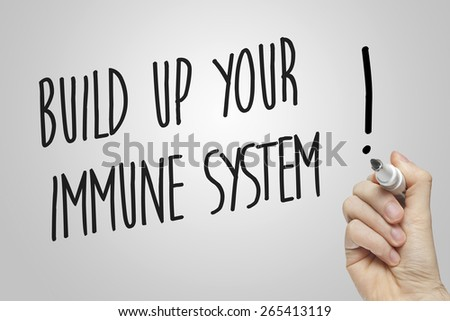 Hand writing build up your immune system on grey background - stock photo