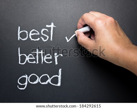 Hand writing correct mark with chalk on the best choice - stock photo