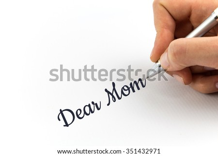 """Hand writing """"Dear Mom"""" on white sheet of paper. - stock photo"""