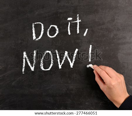 Hand writing Do it , Now! with chalk on a blackboard - stock photo