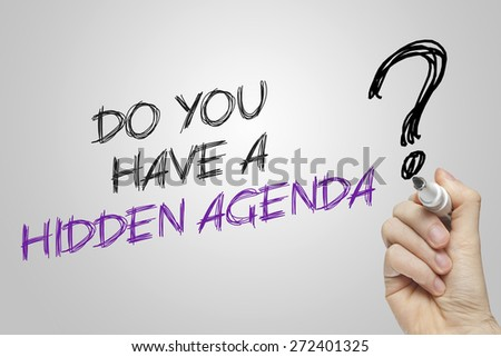 Hand writing do you have a hidden agenda on grey background - stock photo