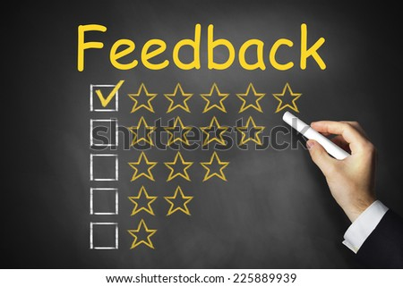 hand writing feedback on black chalkboard golden rating stars ranking