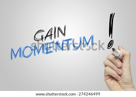 Hand writing gain momentum on grey background - stock photo