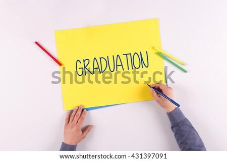 Hand writing Graduation on yellow paper - stock photo