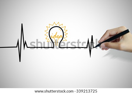 hand writing heartbeat with light bulb idea , business idea , business concept ,Innovation concept - stock photo