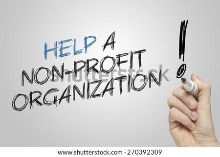 Hand writing help a nonprofit organization on grey background - stock photo