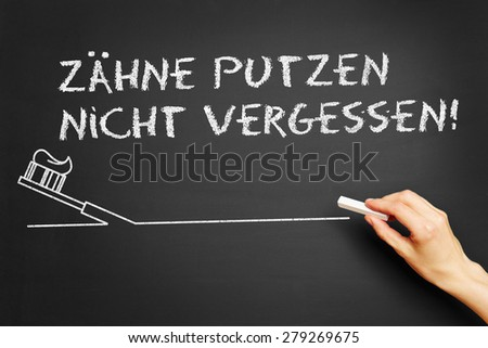 "Hand writing in German ""Zaehne putzen nicht vergessen!"" (Brush your teeth!) on blackboard - stock photo"