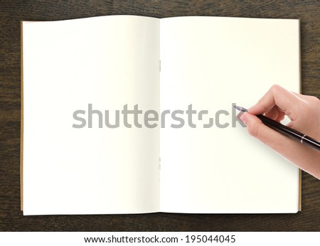 Hand writing in open book on table - stock photo