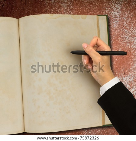 Hand writing in open old notebook on table - stock photo