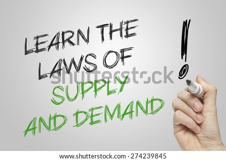 Hand writing learn the laws of supply and demand on grey background - stock photo