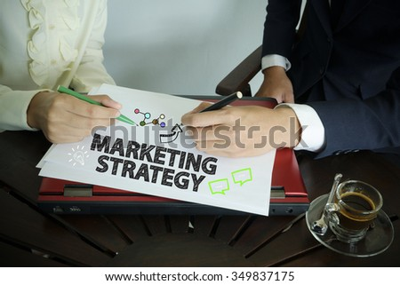 hand writing MARKETING STRATEGY text with two business person , team work concept - stock photo