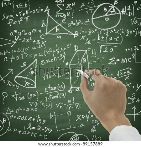 Hand writing maths formula on chalkboard - stock photo