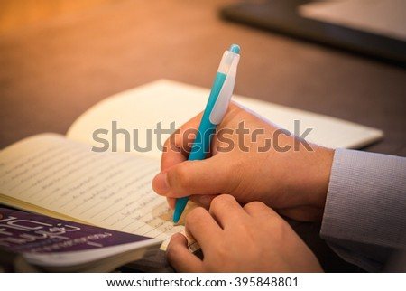 Hand writing note in notebook in business conference room