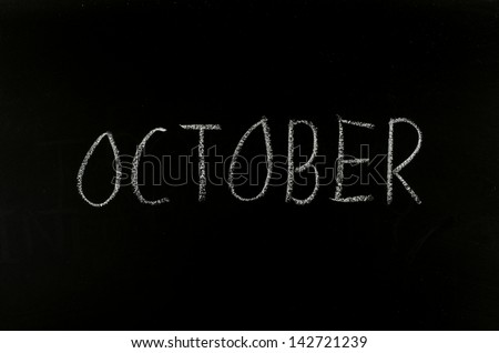 "hand writing ""october"" on blackboard"