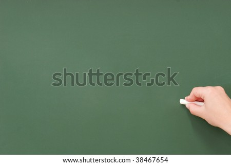 Hand writing on a blank blackboard with white chalk. - stock photo