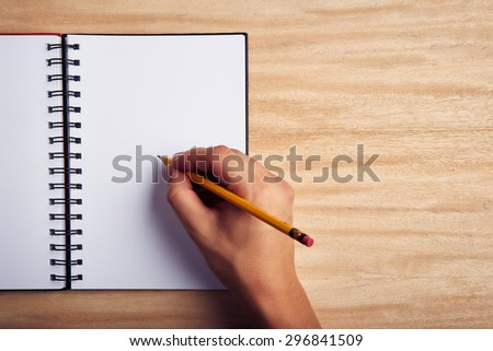 Hand writing on a blank empty notebook - stock photo