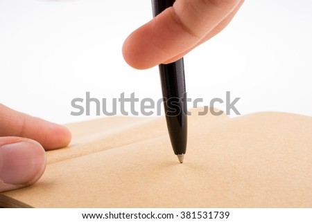 Hand writing on a notebook with a pen - stock photo
