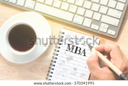 Hand writing on book message MBA. A keyboard and a glass coffee table.Vintage tone. - stock photo