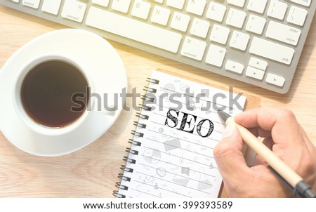 Hand writing on book message SEO. A keyboard and a glass coffee table.Vintage tone. - stock photo