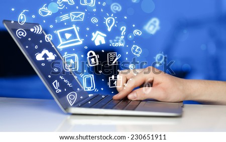 Hand writing on notebook computer with media icons and symbols comming out - stock photo