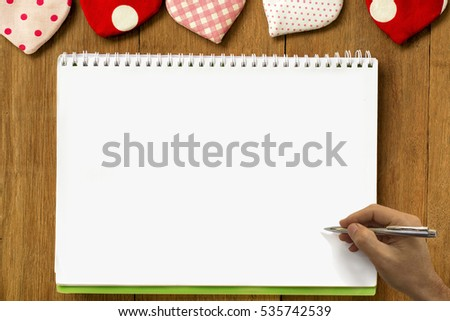 hand writing on notebook with valentine's hearts on wood background