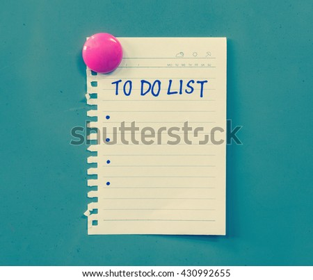 Hand writing on paper with to do list words attached with pink magnet on steel board, colored filter effect - stock photo